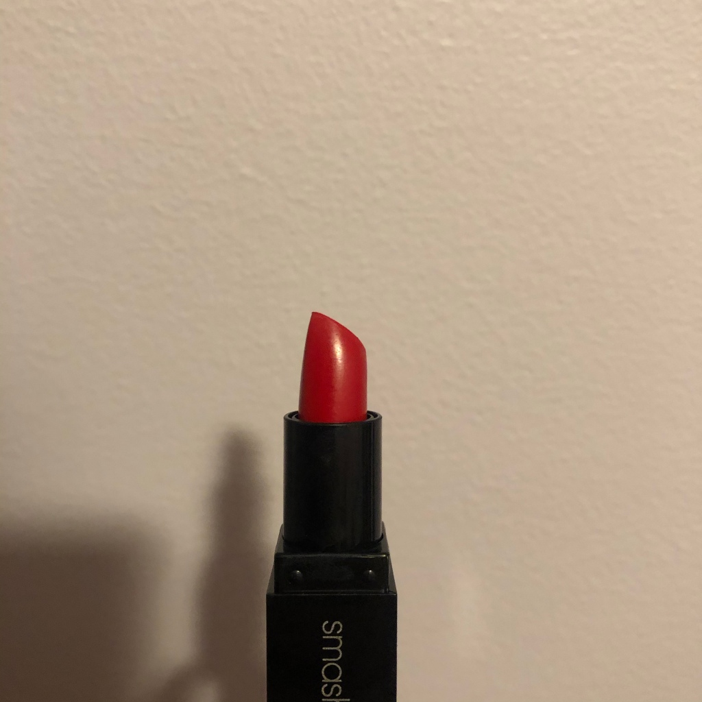 A photo of Smashbox Be Legendary Lipstick in shade Bing Matte with the package opened to reveal the bright blue red lipstick bullet.