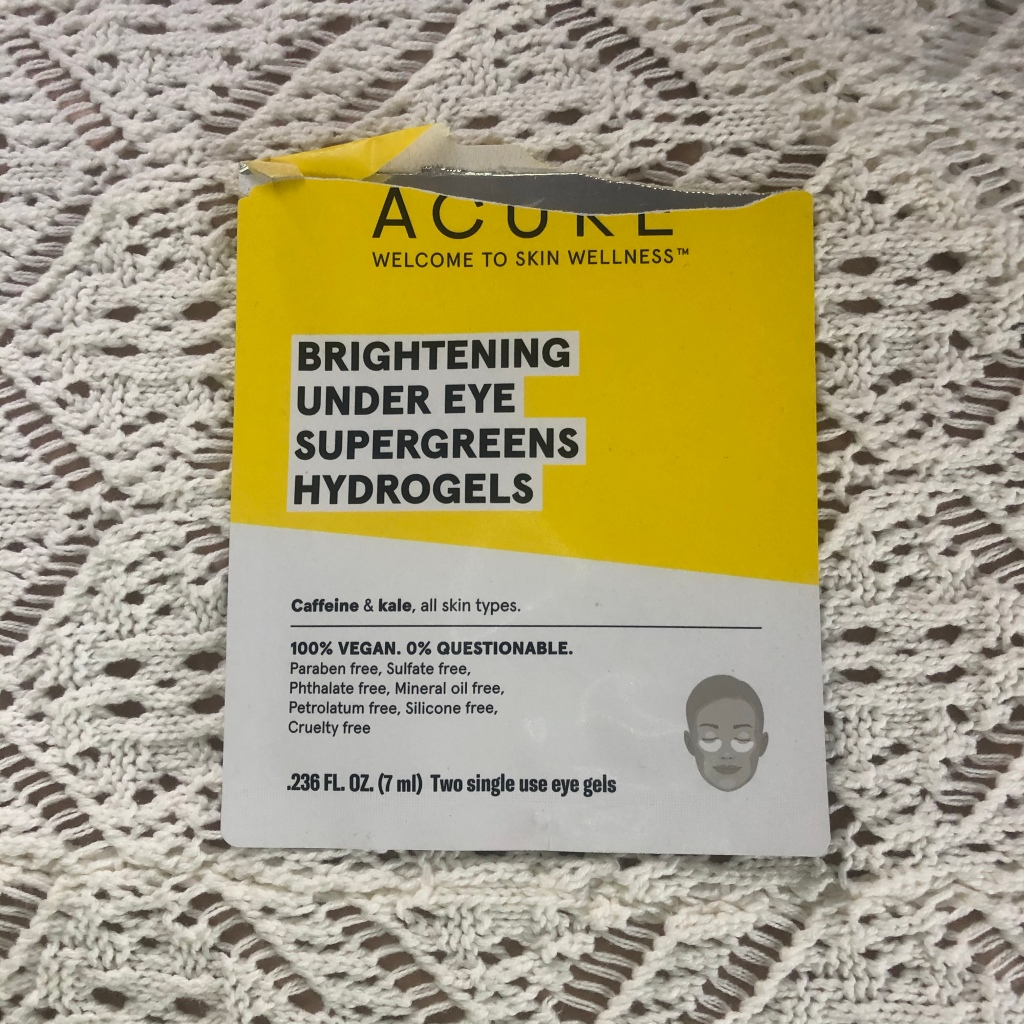 A picture of an opened pack of Acure hydrogel eye patches resting on white crochet background.