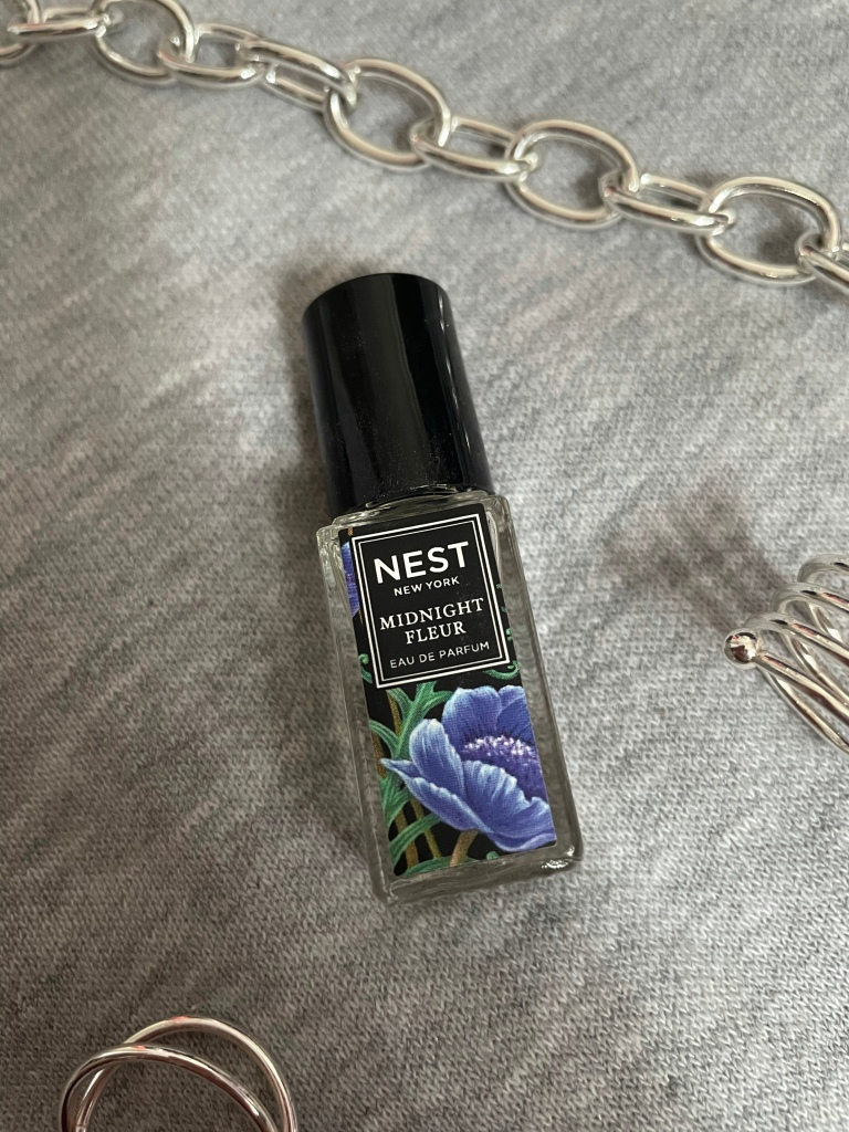 A picture of the travel size fragrance Midnight Fleur from NEST New York Fragrances on a gray background surrounded by silver jewelry.