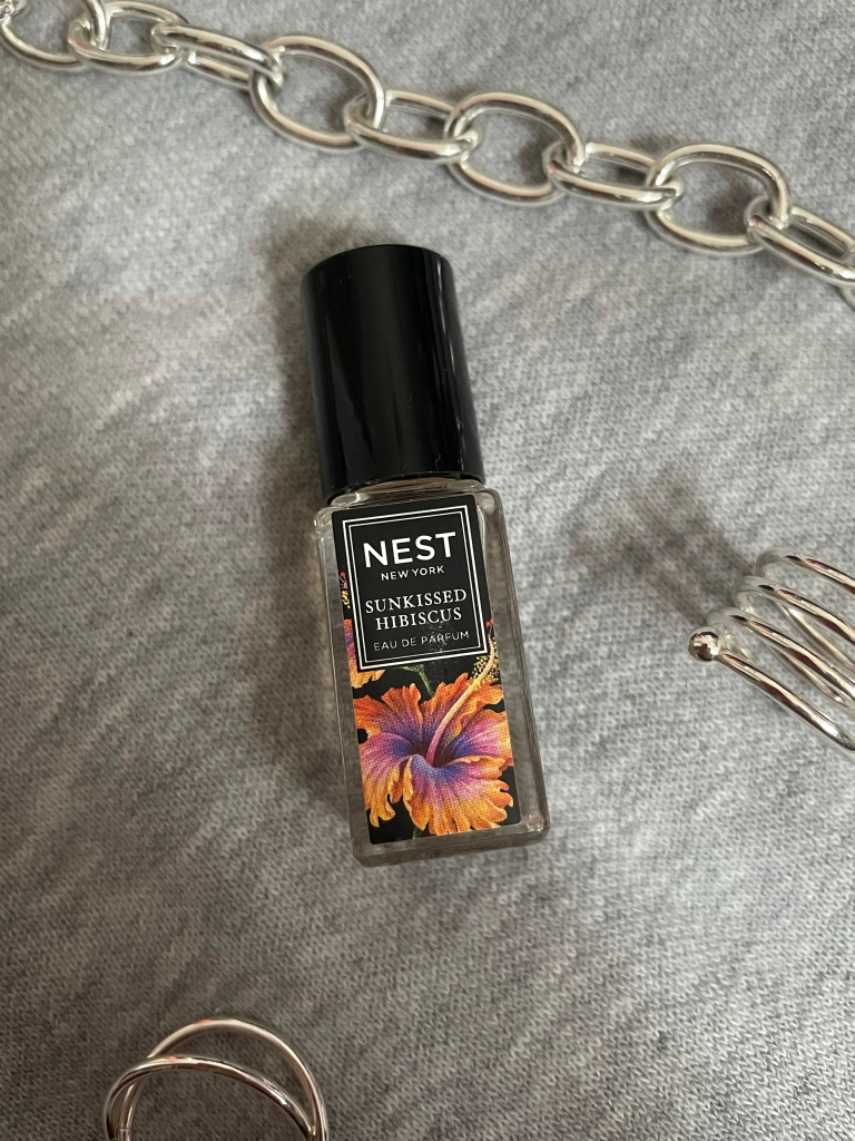 A picture of the travel size fragrance Sunkissed Hibiscus from NEST New York Fragrances on a gray background surrounded by silver jewelry.