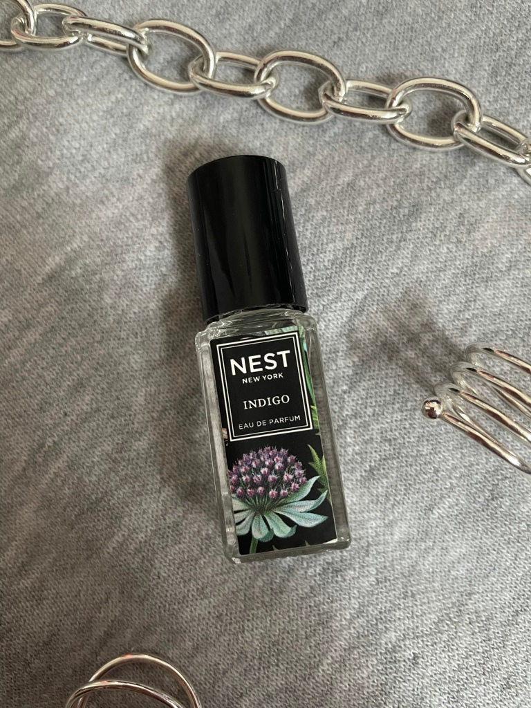 A picture of the travel size fragrance Indigo from NEST New York Fragrances on a gray background surrounded by silver jewelry.